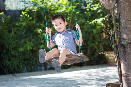 kid portrait: Asian baby boy playing on a swing and having fun in park