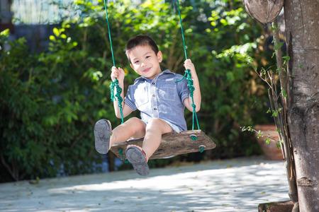 columpios: Bebé asiático que juega en un columpio y divertirse en el parque Foto de archivo