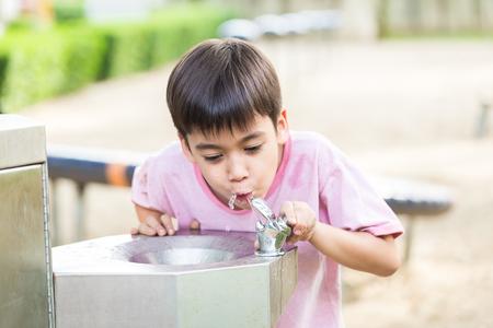 people drinking water: Little boy drinking water in the public park