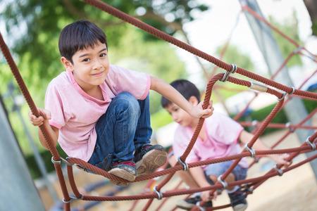 niño trepando: Niño pequeño que sube la actividad obstáculo cuerda asiático en el patio