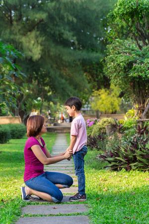 mujeres y niños: Madre sentada en el parque tomados de la mano y enseña a su hijo