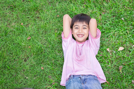 lay down: Little boy lay down on the grass with smile face