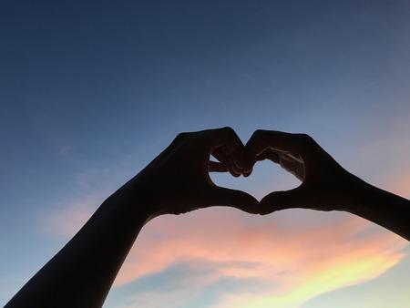 남자 손 일몰, 발렌타인 데이 컨셉 때 어두운 파란색과 주황색 하늘에 심장 모양의 기호를 확인 스톡 콘텐츠