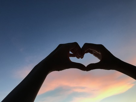 man hands make heart shape symbol up into the dark blue and orange sky when sunset, valentines day concept