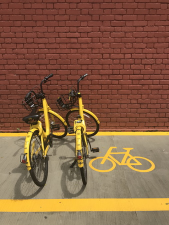 Everton Park building, Singapore – February 4, 2018: rental by application two of ofo brand bicycles parking in parking lot in front of Everton Park building, Singapore