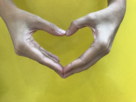 woman's hands make heart shape symbol with bright yellow background in day light 版權商用圖片