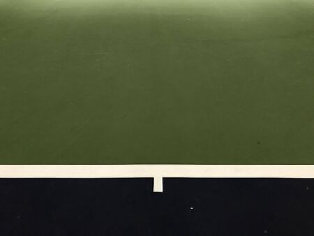 frame of dark blue and white lines and dark green surface at the end of tennis indoor court, using for background
