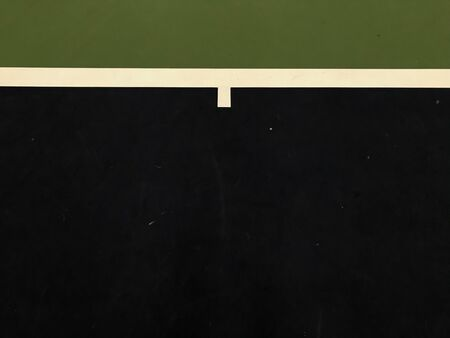top view of dark blue and white lines and dark green surface at the end of tennis indoor court, using for background