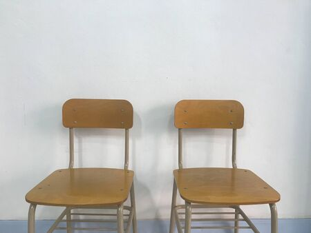 two brown empty school chairs with white wall on background in natural daylight Stockfoto