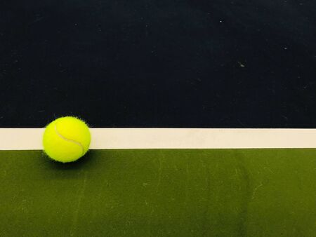 green tennis ball at the left end white line of tennis indoor court in natural daylight