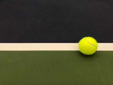 green tennis ball at the right end white line of tennis indoor court in natural daylight 写真素材