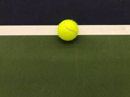 green tennis ball at the middle end white line of tennis indoor court in natural daylight