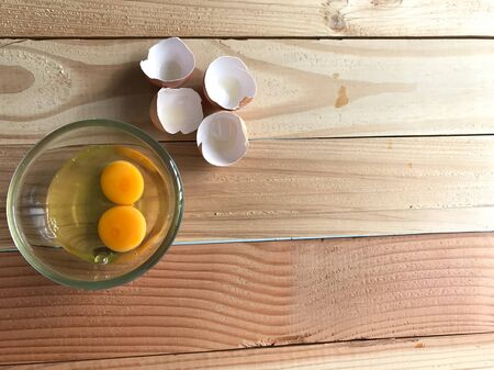 studio top view shot of two fresh yolk and egg white in clear glass cup and four eggshells beside it on natural rubber wood board with copy space on right side of frame
