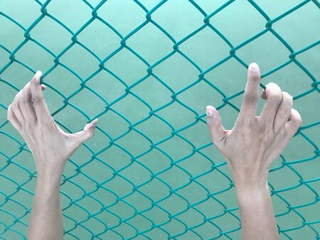man's hands are grabing green iron bar, tightly, with light green wall on background, unfree concept Banco de Imagens