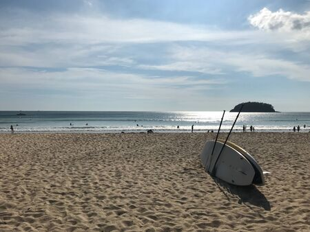 two surfboards and paddles on beach with many people in the sea on sunshine day Reklamní fotografie