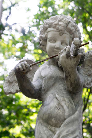 Decorative cupid playing violin sculpture in the garden