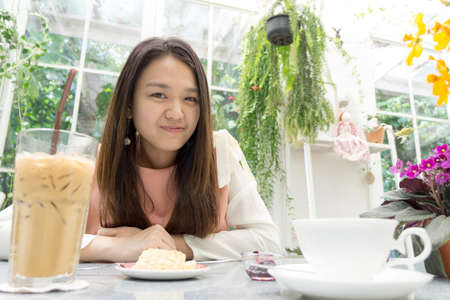 Asian young lady on the dining table with decorative flower and tree