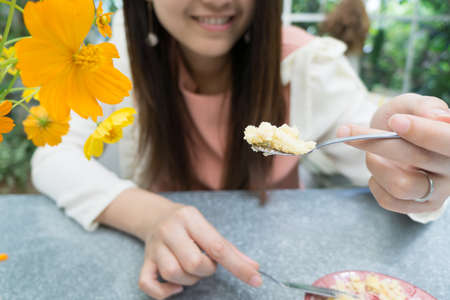 Asian young lady is feeding food on the dining table Stockfoto