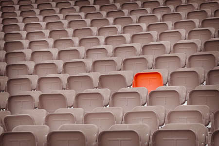 One red chair standout from background of desaturated chairs in the stadium