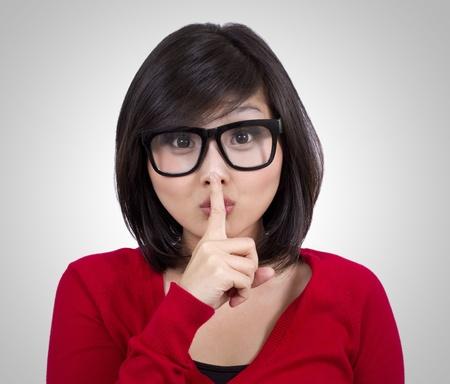 bella ragazza adolescente con gli occhiali nerd o facendo segno il silenzio