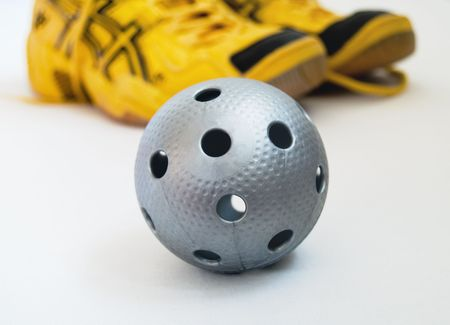 A gray floorball ball and yellow shoes. Focus on the ball.