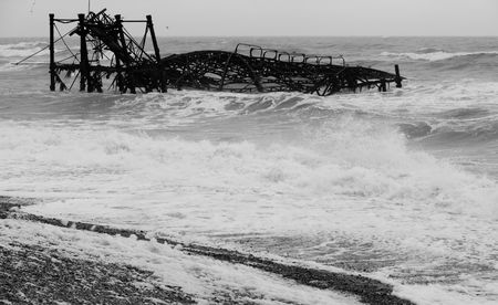 The collapsed and burned Brighton West Pier in a stormy weather.