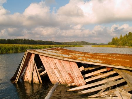 boathouse: A weathered and fallen down boathouse at the ocean.