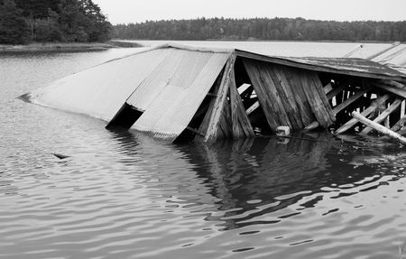 A weathered and fallen down boathouse at the ocean. Black and white.
