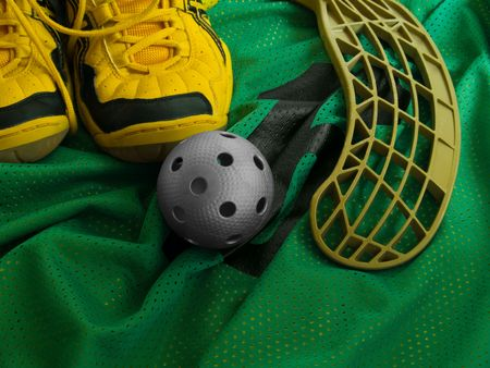 Floorball ball, stick, and shoes on a green jersey.