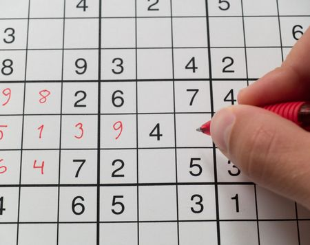A hand holding a pen on a sudoku grid.