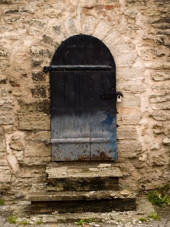 An aged wooden door on a stone wall. photo