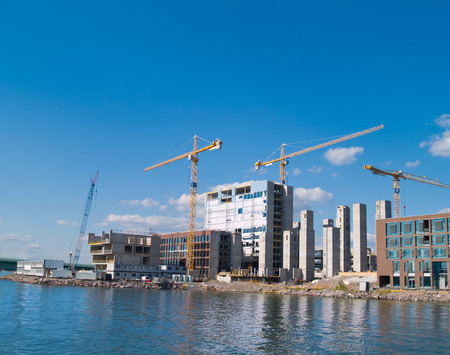 A construction site with multiple cranes on the waters edge