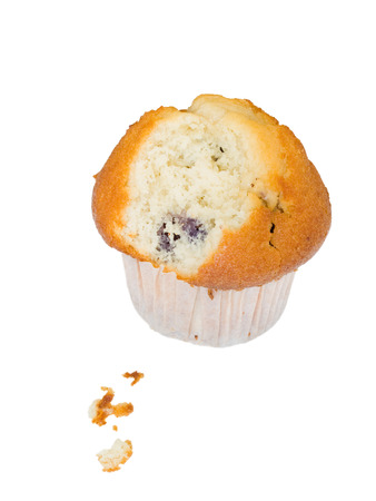 A blueberry muffin on a white background. One bite has already been taken, small crumbs on the foreground.