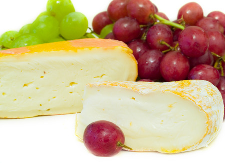 matured: Cheeses with green and red grapes on a white background Stock Photo