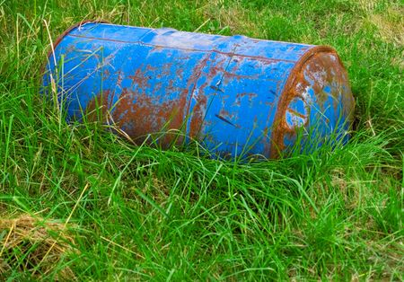 A rusty blue barrel lying in grass.
