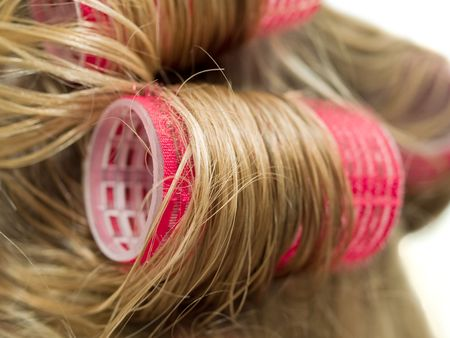 A close-up of red curlers in blond hair Stock Photo