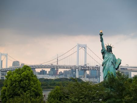 The statue of Liberty in Odaiba, Tokyo with the Rainbow Bridge and Tokyo Tower in the background