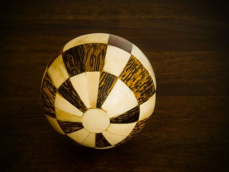 A ball made of wooden pieces on a wood background Stock Photo