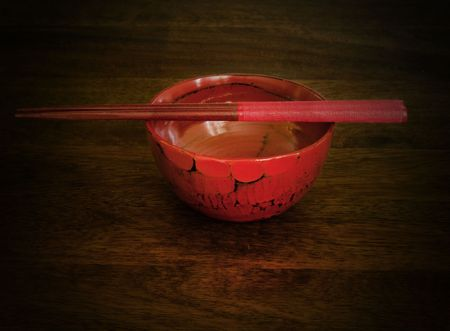 Red chopsticks and a bowl on wooden table