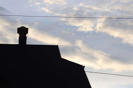 silhouette of a house with a chimney on the background of a cloudy bright sky