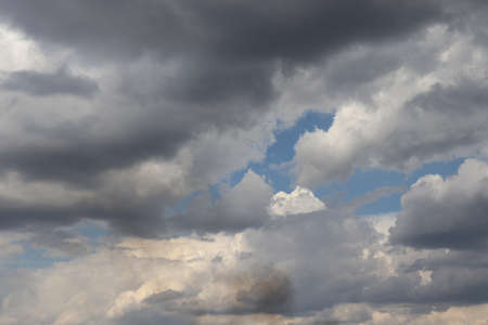 on the blue sky white and gray clouds, a clot of gray smoke on the background of clouds