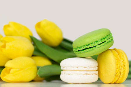 French Colorful Macarons on a White Background with Flowers