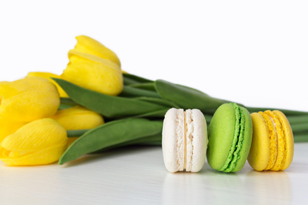 Bright French Dessert with a Bouquet of Flowers on a White Background. Spring Concept