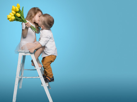 Boy Kisses Girl and Gives Flowers. Copy Space Stock Photo