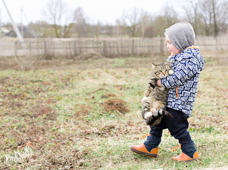 coercion: A little Boy Forcibly Carries a Sad Cat Stock Photo