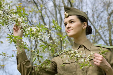 Portrait of a Russian Military Woman in a Blooming Garden