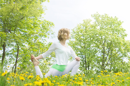Woman Practicing Yoga Outdoors in Summer