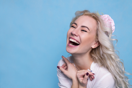 Beautiful young girl with flower in hair laughing. Copy Space 스톡 콘텐츠