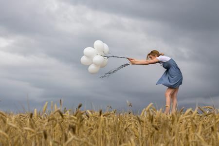 Femme fragile garde les ballons contre le vent fort