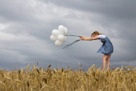 Fragile Woman Keeps Balloons Against Strong Wind